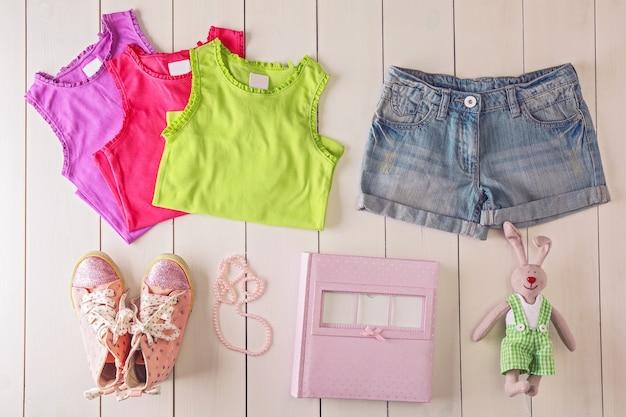 Vêtements et accessoires pour enfants à plat sur une surface en bois