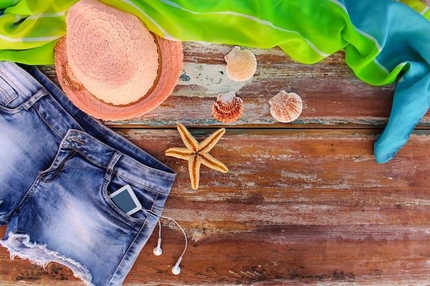 Vêtements et accessoires pour femmes d'été: chapeau, short en jean, paréo, coquillages, téléphone portable, écouteurs.