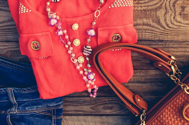 Vêtements et accessoires pour femmes: pull, jeans, sac à main, perles sur fond en bois. image tonique.