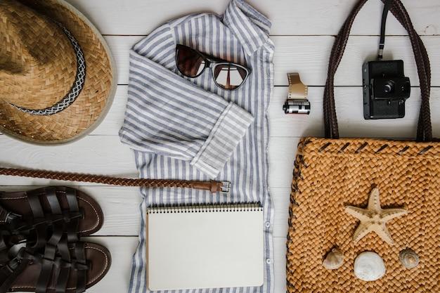 Vêtements et accessoires touristiques méditerranéens pour femme sur fond de table en bois blanc