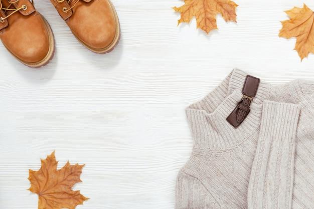 Vêtements d'automne féminins, bottes en daim orange, pull chaud en tricot décoré de feuilles d'automne en érable. mise à plat avec des vêtements confortables et un espace de copie sur un bureau en bois blanc.