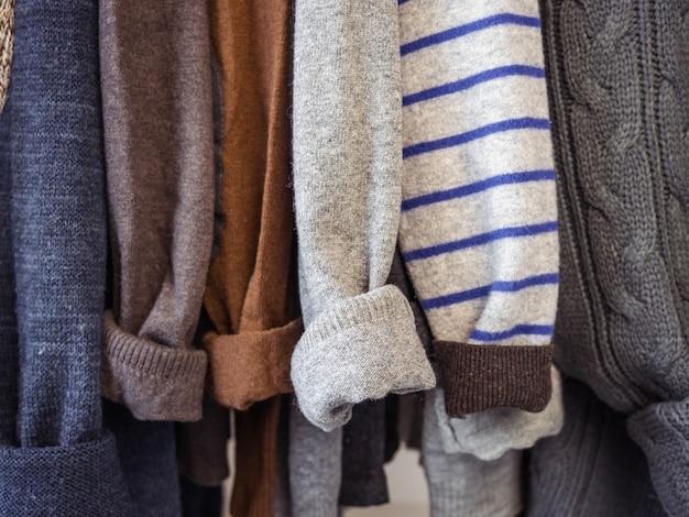 Vêtements d'automne et d'hiver accrochés à des cintres dans le dressing. pas de monde, gros plan. concept de beauté et de mode