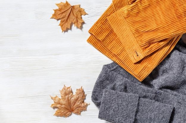 Vêtements d'automne pour femmes, pull en laine gris chaud et pantalon orange en velours côtelé. concept de vue d'ensemble de magasinage avec copie espace. vue de dessus. mise à plat.