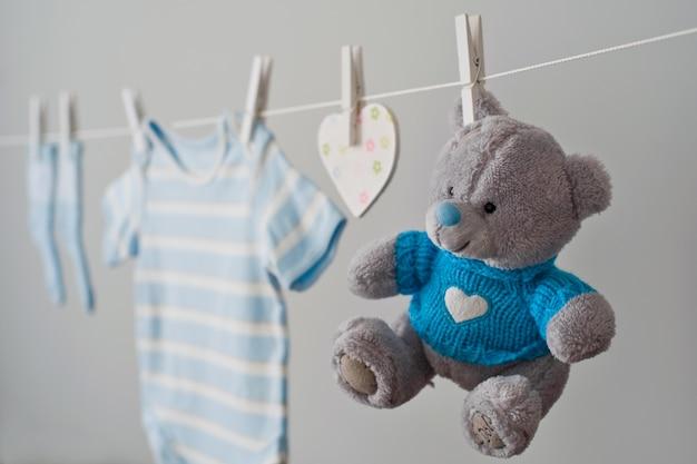 Vêtements de bébé bleu sur la corde à linge