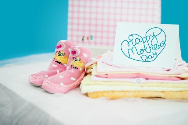 Les vêtements de bébé avec une boîte-cadeau sur fond bleu. concept de bonne fête des mères