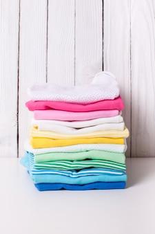 Vêtements de bébé colorés de pile pliée sur fond blanc