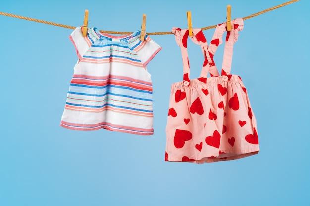 Vêtements de bébé fille épinglés sur une corde à linge contre bleu