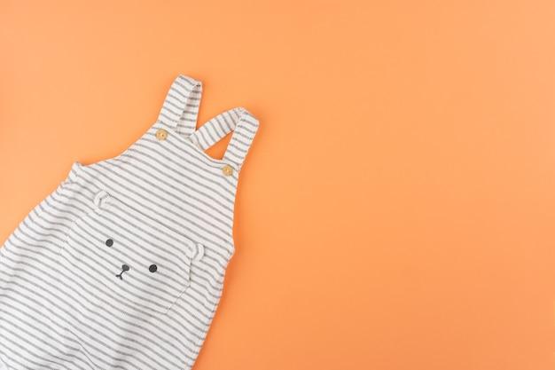 Vêtements de bébé fille sur fond orange vue de dessus