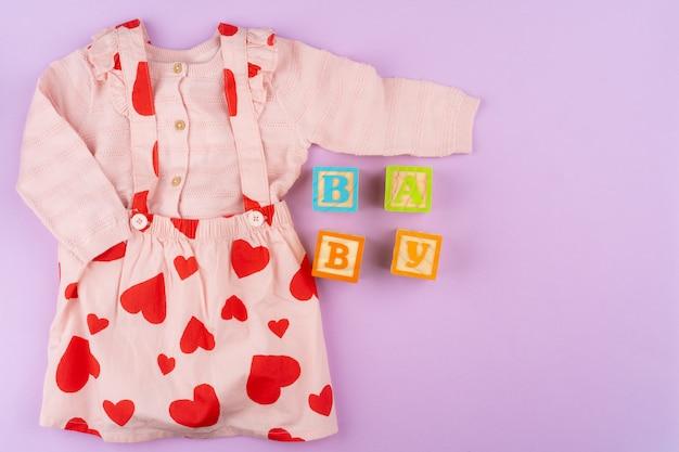 Vêtements bébé fille sur fond pastel lilas