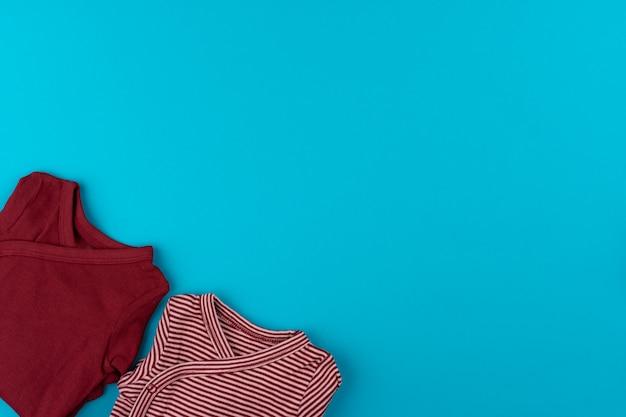 Vêtements bébé sur fond bleu vue de dessus