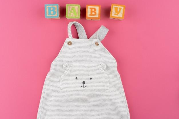 Vêtements bébé sur fond rose vue de dessus