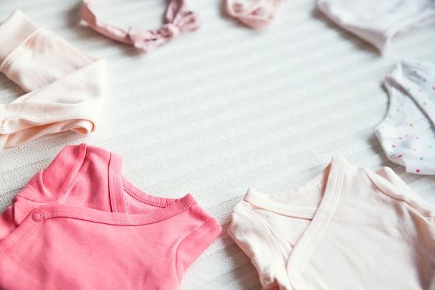 Vêtements de bébé sur fond de tissu pastel clair ambiance douce et confortable