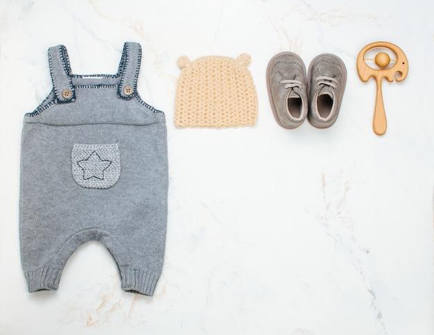 Vêtements de bébé nouveau-né et pouf sur marbre clair