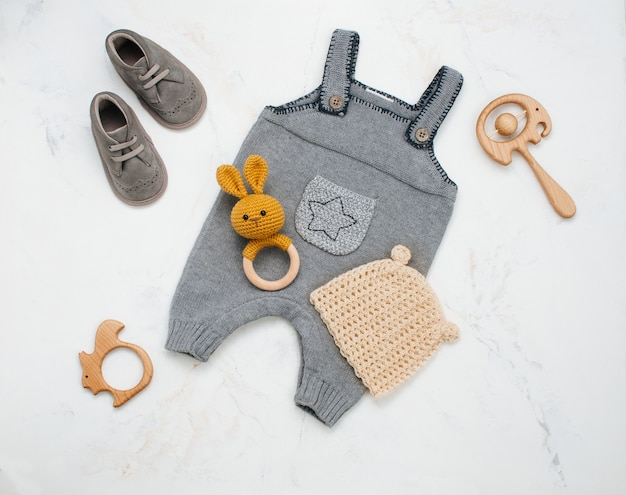 Vêtements de bébé nouveau-né et pouf sur marbre