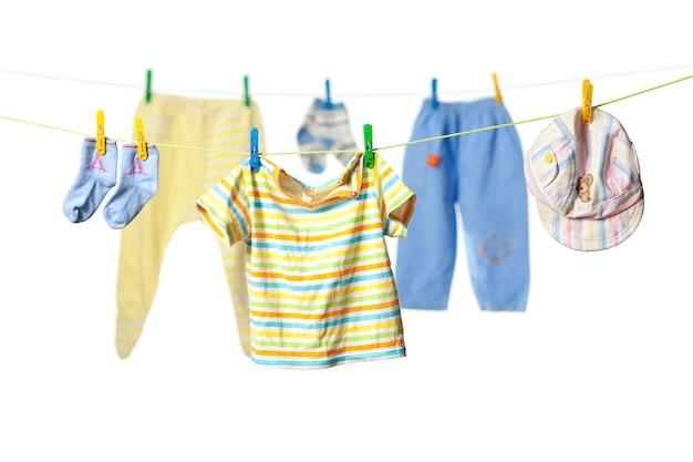 Vêtements de bébé séchant sur une corde isolé sur fond blanc
