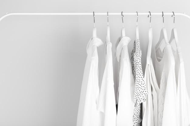 Vêtements blancs suspendus sur une grille