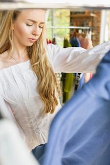 Vêtements, boutique de vêtements pendant les soldes, collection été ou automne. jeune femme essayant un tissu, à la recherche d'une nouvelle tenue. concept de mode, style, offres, émotions, ventes, achats. tout nouveau shopping.