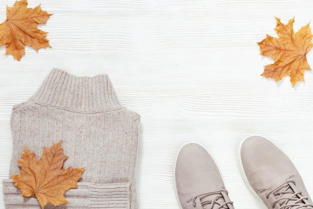 Vêtements chauds d'automne. pull en laine gris tendance et chaussures de confort sur un fond en bois blanc avec espace de copie.