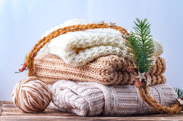 Des vêtements chauds et pastel, des écharpes tricotées de couleur pastel et une pelote de laine à tricoter. hiver, vêtements d'automne.
