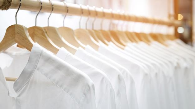 Vêtements chemises blanc sur rail suspendu à des cintres.