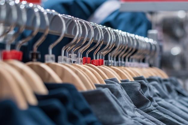 Vêtements sur des cintres sur des supports dans le marché de masse