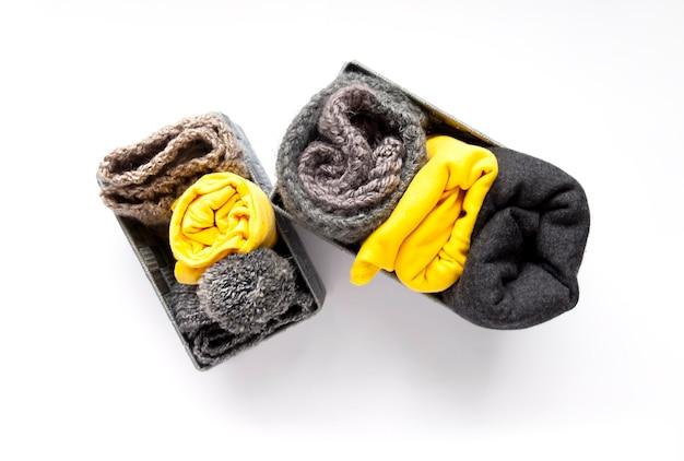 Vêtements colorés dans de petites boîtes textiles sur fond blanc. couleurs tendance jaunes et grises. t-shirts et pulls roulés. organisation compacte de garde-robe à la maison. stockage vertical domestique