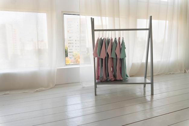 Des vêtements colorés pour enfants sont suspendus à un cintre dans un magasin, espace de copie