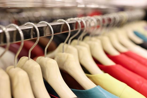 Des vêtements colorés sont suspendus à des cintres dans un centre commercial