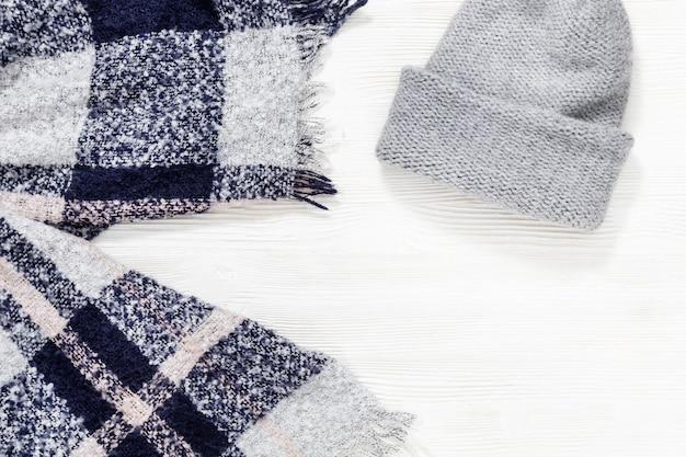 Vêtements confortables d'automne. écharpe chaude, bonnet tricoté sur fond de bois blanc. vêtements féminins. tenues de mode décontractées. mise à plat. vue de dessus.