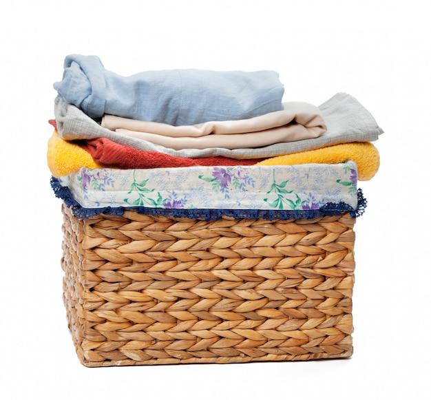 Vêtements dans un panier à linge en bois isolé sur blanc