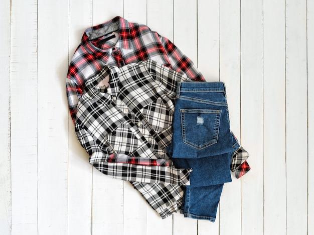 Vêtements . deux chemises à carreaux et des jeans sur un bois. vue de dessus