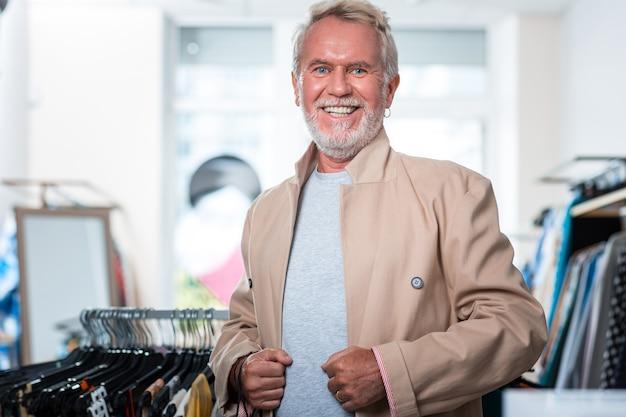 Des vêtements élégants. taille de bel homme aux cheveux gris exprimant la joie tout en étant vêtu d'une nouvelle veste à la mode
