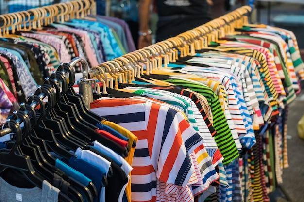 Les vêtements d'été des hommes et des femmes les pulls molletonnés les pantalons les maillots les manteaux les vestes sur le cintre en