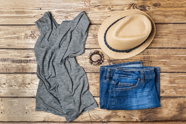 Vêtements d'été pour femmes. photo de mode plat laïque. blue jeans, t-shirt, chapeau de soleil sur fond en bois.