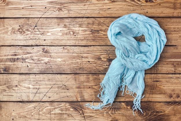 Vêtements d'été pour femmes. photo de mode plat laïque. foulard bleu clair sur fond en bois. espace de copie