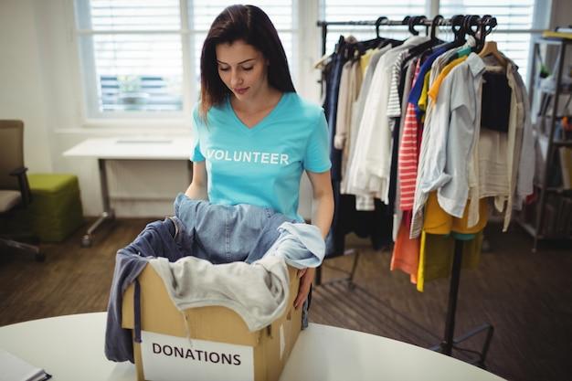 Les vêtements féminins bénévoles tenant en boîte de dons