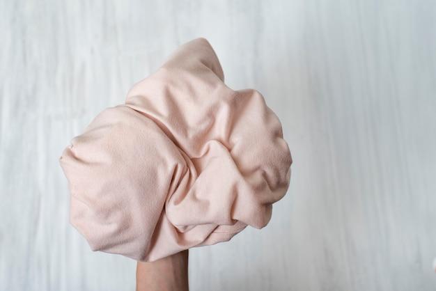 Des vêtements froissés dans une main féminine. fermer