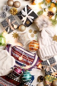 Vêtements d'hiver femme plat poser avec lumières, décorations, boîtes-cadeaux noires, pommes de pin.