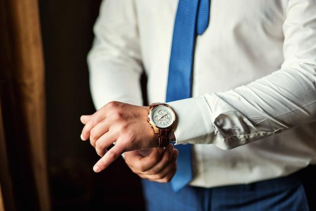 Vêtements d'horloge homme d'affaires, homme d'affaires vérifiant l'heure sur sa montre-bracelet. main d'homme avec une montre, montre sur la main d'un homme, les honoraires du marié, la préparation du mariage, la préparation au travail