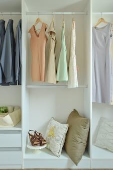 Vêtements masculins et féminins suspendus sur des cintres dans une armoire
