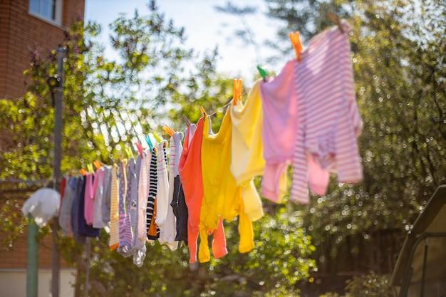 Vêtements mignons pour bébé accrochés à la corde à linge en plein air. linge enfant suspendu en ligne dans le jardin sur fond vert. accessoires bébé.