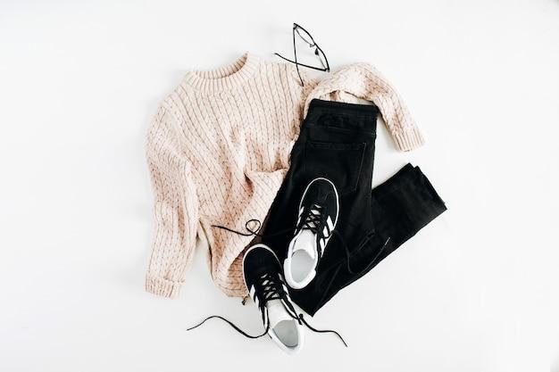 Les vêtements de mode hiver femmes regardent sur une surface blanche