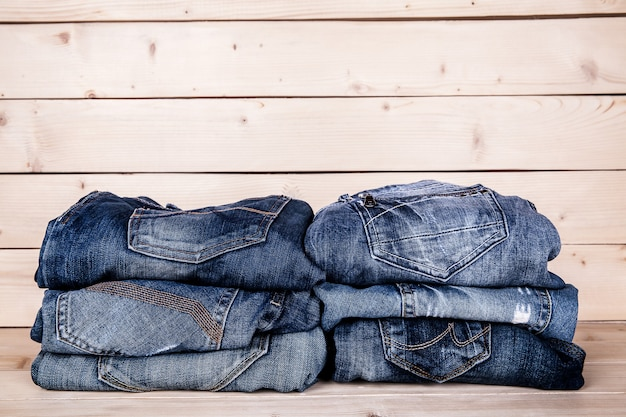 Vêtements à la mode. tas de jeans sur un fond en bois