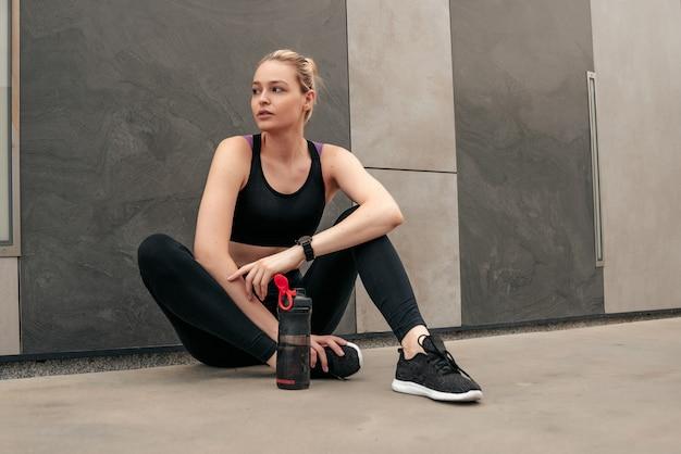 Vêtements noirs pour le sport, femme en hauts de sport, fille au mur, une fille assise sur un sol en béton, fille avec un shaker