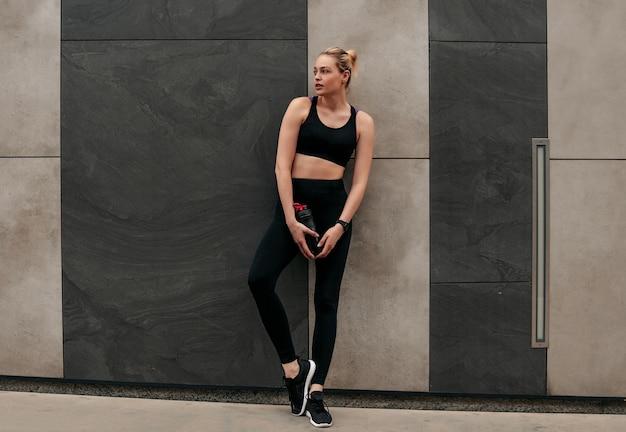 Vêtements noirs pour le sport, femme en hauts de sport, fille au mur, fille avec un shaker