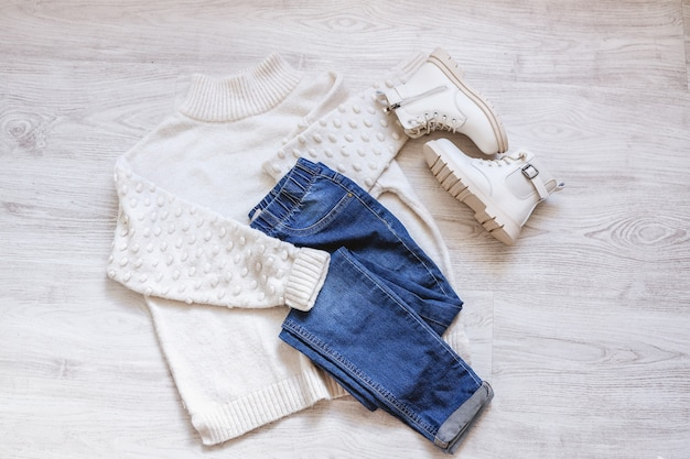 Vêtements plats d'automne pour femmes avec pull blanc chaud, jeans bleus et chaussures blanches, tenue féminine à la mode sur drap blanc, espace de copie.