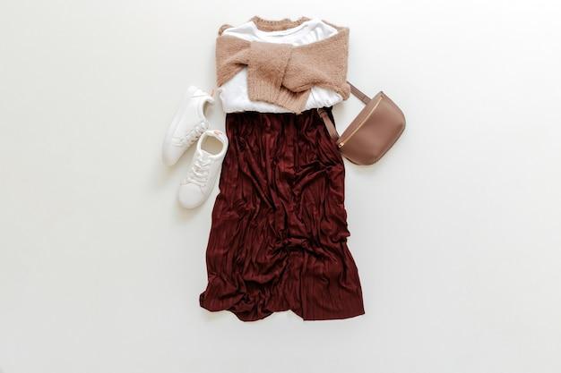 Vêtements pliés pour femme mode tenue basique urbaine. look de printemps féminin tenue d'automne jupe bordeaux pull beige chaussures blanches baskets sac t-shirt de base blanc sur fond blanc vue de dessus à plat.