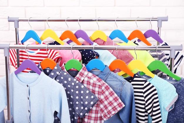 Vêtements pour enfants sur des cintres dans une pièce