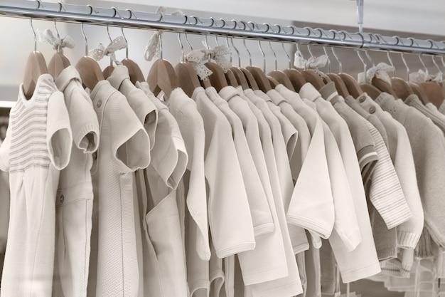 Des vêtements pour enfants en tissus naturels sont suspendus à des cintres.