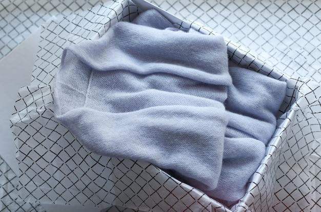 Vêtements pour femmes de couleur pastel plié dans une boîte sur fond blanc. concept d'organisation de cadeaux